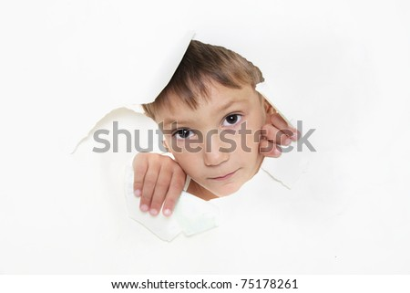 young boy peeping through hole in paper - stock photo