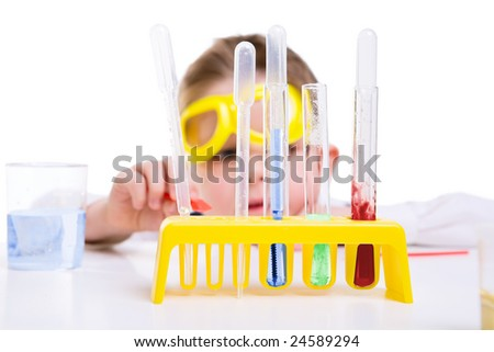 Young boy performing chemistry experiments with different liquids. - stock photo