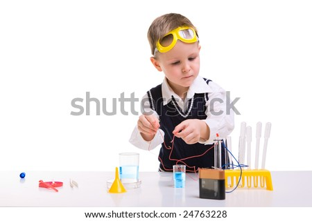Young boy performing experiments with battery and small lamp. - stock photo