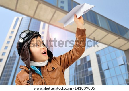 Young boy pilot with a paper plane - stock photo