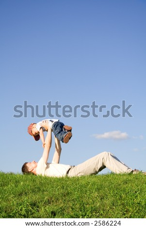 Young boy play with father. Green grass. Blue sky. 3 - stock photo
