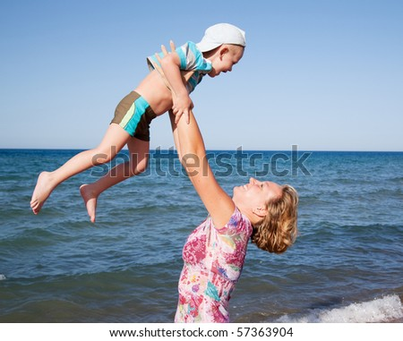 Young boy play with mother. Mother throwing her son into the air. On a beach. - stock photo