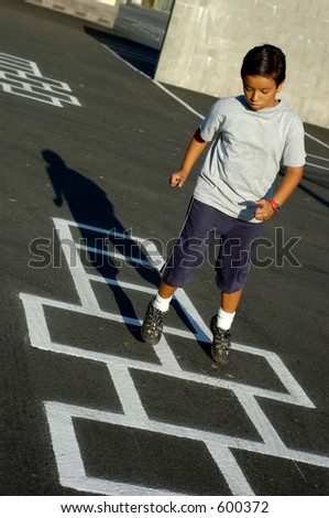 Young boy playing a game of hopscotch. - stock photo