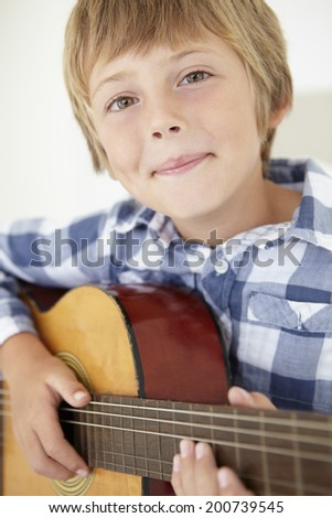 Young boy playing acoustic guitar - stock photo