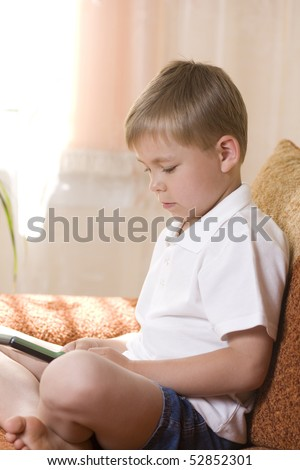 Young boy playing an electronic game - stock photo