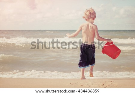 Young boy playing at the beach - stock photo