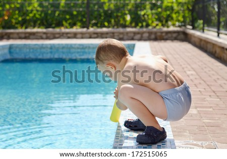 Young boy playing at the edge of a swimming pool in his costume and shoes as he prepares to put something in the cool blue water on a hot sunny day - stock photo