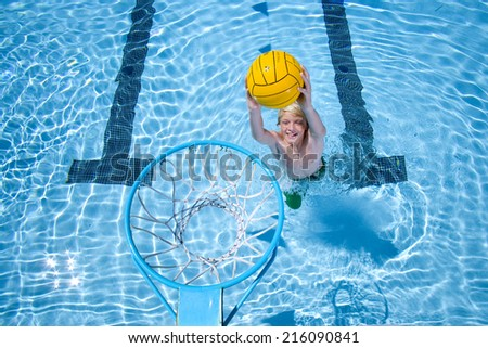 Young boy playing basketball in swimming pool - stock photo