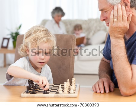 Young boy playing chess with his grandfather at home - stock photo