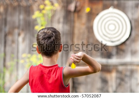 Young boy playing darts outdoor