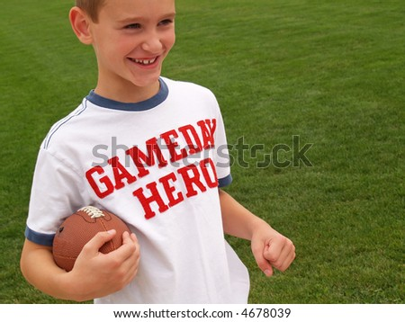"young boy playing football and wearing a ""gameday hero"" shirt - stock photo"