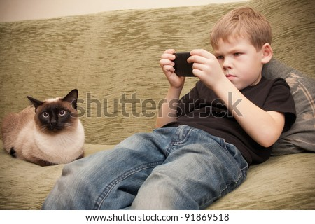 Young boy playing games with your mobile phone or reading a text message - stock photo