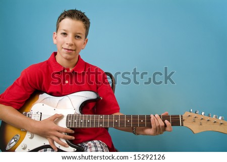 Young boy playing his guitar - stock photo