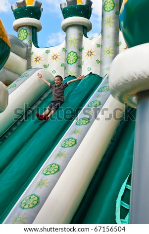 Young boy playing in inflatable playground - stock photo