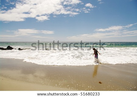 Young boy playing in ocean - stock photo
