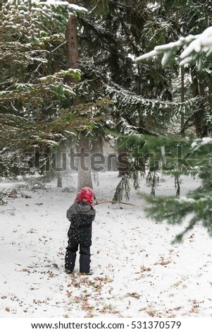 Young boy playing in snow forrest