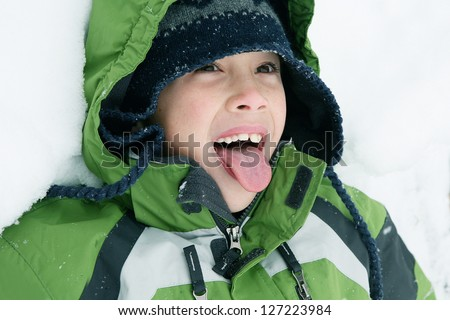 Young Boy Playing in Snow Trying to Catch Snowflakes on his Tongue