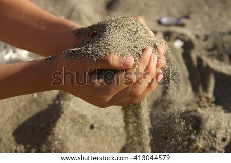 Young boy playing in the sand at the beach on a sunny summer day.  - stock photo