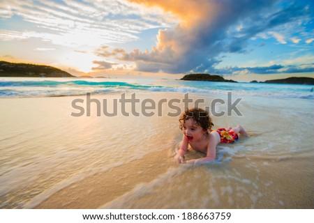 Young boy playing in the surf, Cinnamon Bay, St. John, USVI - stock photo