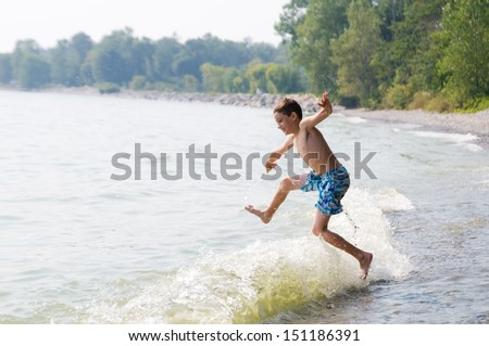 young boy playing in the waves at a beach - stock photo