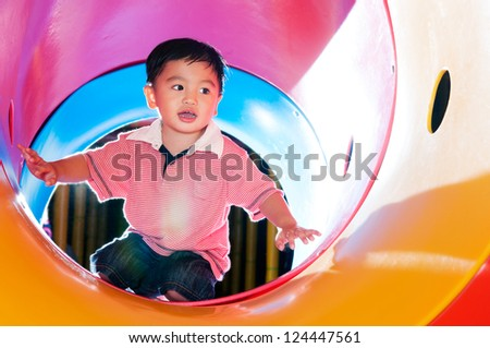 Young boy playing in tube slide