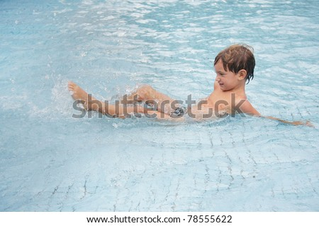 young boy playing in water pool - stock photo