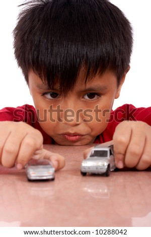young boy playing indoor with model cars - stock photo