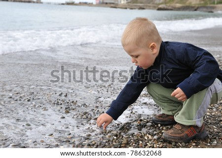 Young boy playing near the sea. - stock photo