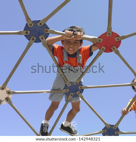 Young boy playing on a play structure - stock photo