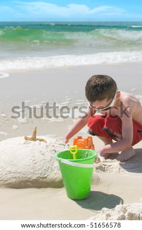 Young  boy playing on beach - stock photo