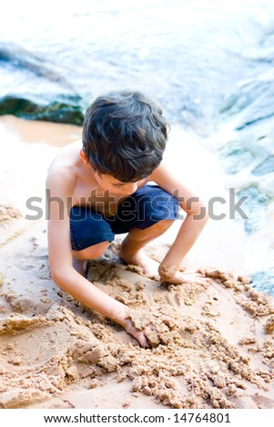 Young boy playing on the sandy beach.