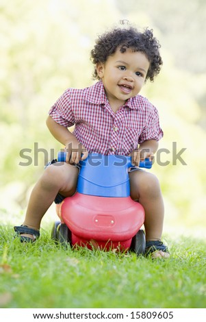 Young boy playing on toy with wheels outdoors - stock photo