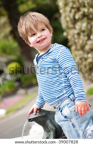 Young boy playing on water fountain - stock photo