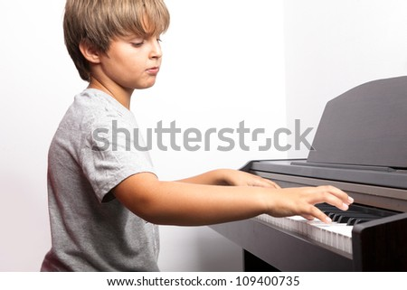 Young boy playing piano - stock photo