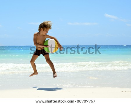 young boy playing running and jumping on the tropical beach with a ball - stock photo