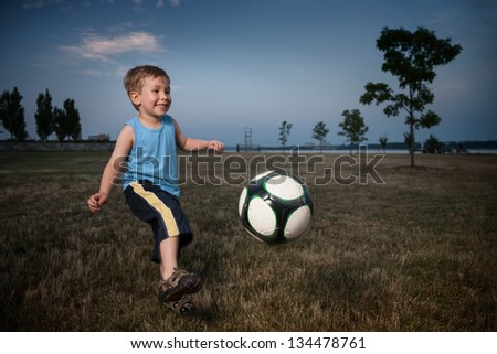Young boy playing soccer ball at twilight in park - stock photo