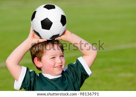 Young boy playing soccer in organized league game - stock photo