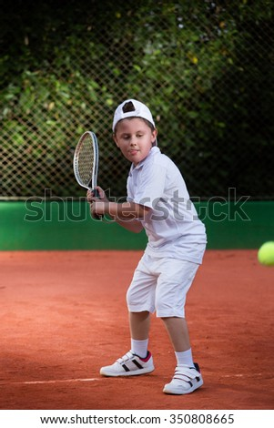 Young boy playing tennis at a clay court - stock photo