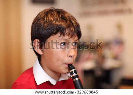Young boy playing the clarinet - shallow depth of field - warm tones. Copy space right. - stock photo