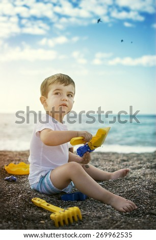 Young boy playing un the beach in casual image with natural light - stock photo