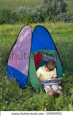 Young boy playing using a lap top,  in camping tent in summer forest - stock photo
