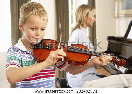 Young boy playing violin accompanied by teacher - stock photo