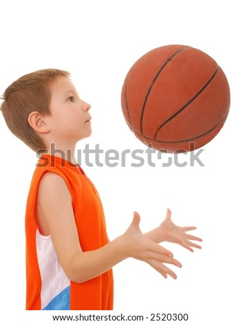 Young boy playing with a basketball isolated on white