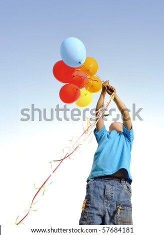 Young boy playing with a bunch of balloons outside - stock photo