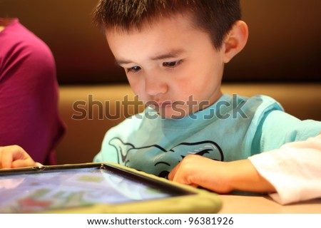 Young boy playing with a touch pad PC tablet.