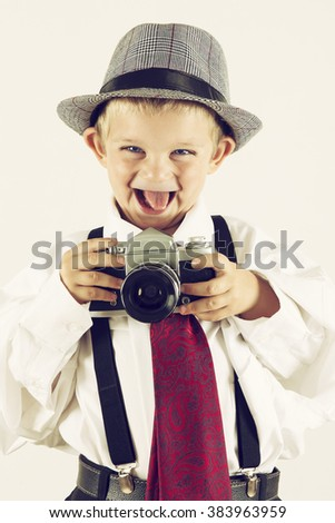 Young boy playing with an old camera to be a photographer