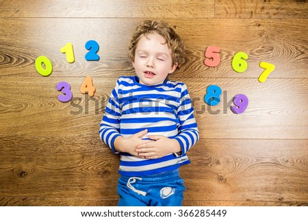 young boy playing with his collection of numbers while sleeping on brown wooden floor - stock photo