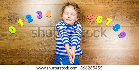 young boy playing with his collection of numbers with happy and smiling face while laying on brown wooden floor - stock photo