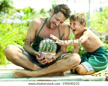 Young boy playing with his father in a green house - stock photo