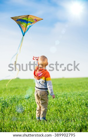 Young boy playing with his kite in a green field.  - stock photo